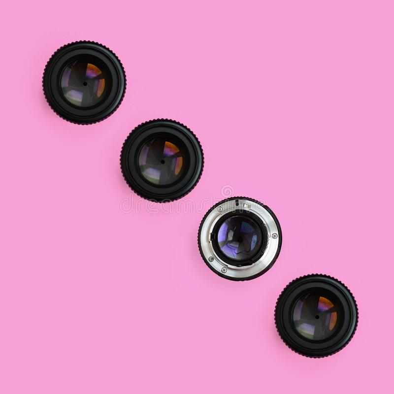 Einige Kameraobjektive mit einer geschlossenen Öffnungslüge auf Beschaffenheitshintergrund des rosa Pastellpapiers der Mode Farbi lizenzfreie stockfotografie