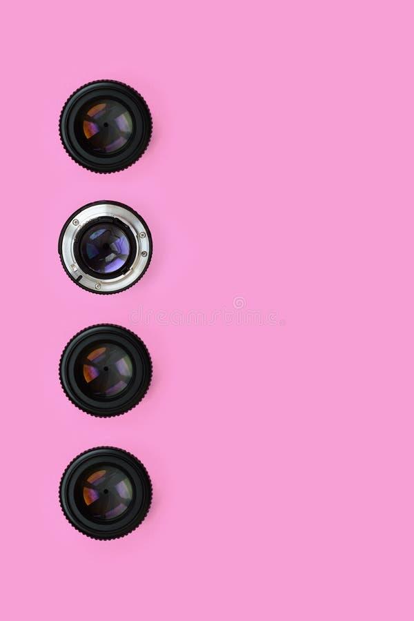 Einige Kameraobjektive mit einer geschlossenen Öffnungslüge auf Beschaffenheitshintergrund des rosa Pastellpapiers der Mode Farbi lizenzfreies stockbild