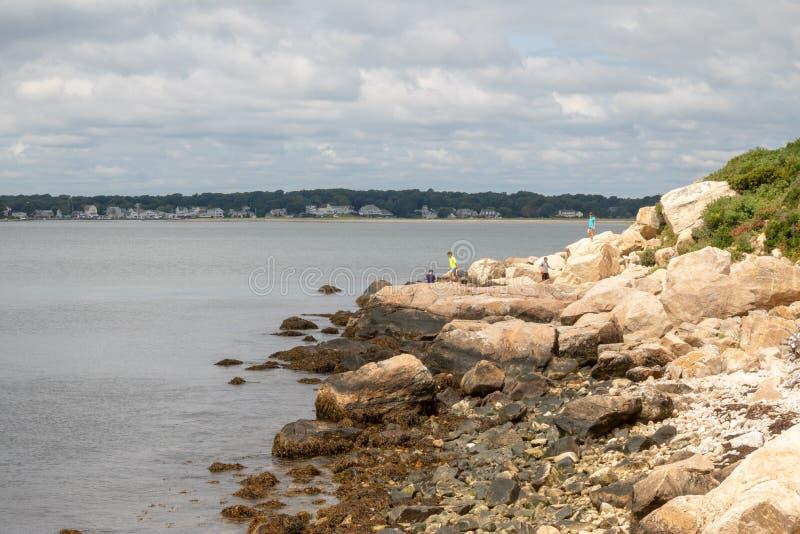 Einige Kinderspiel auf dem Rock auf dem Ufer stockfotografie