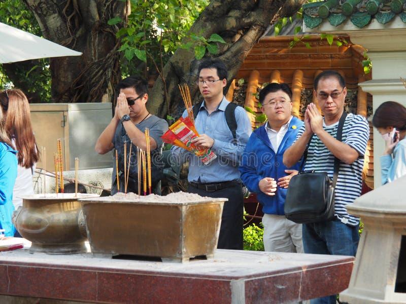 Einige Leute, die im Tempel von Wong Tai Sin in Hong Kong beten lizenzfreie stockfotografie
