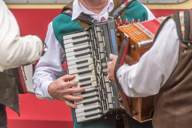 Einige Männer in der traditionellen Kleidung spielen das Akkordeon stockfotos