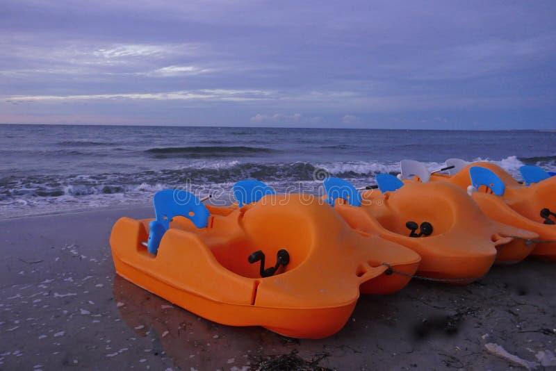 Einige orange Tretboote auf dem Strand zur Sonnenuntergangzeit lizenzfreies stockfoto