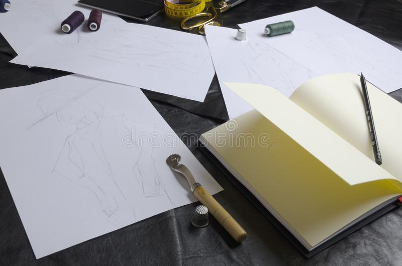 Einige Skizzen während der Arbeit des Designers über Tabelle Werkzeuge für die Schaffung der Kleidungssammlung lizenzfreie stockfotos