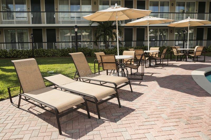 Einige Stühle mit einem Sonnenschirm für das Ein Sonnenbad nehmen durch das Pool florid stockbilder