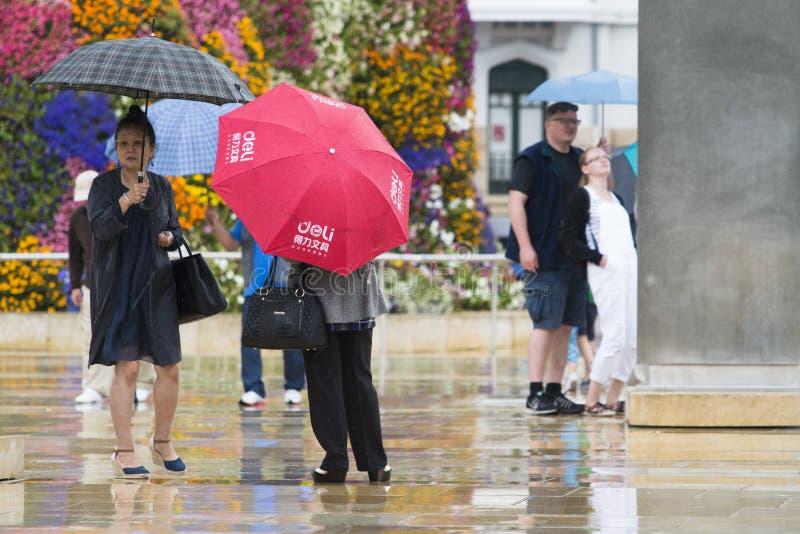 Einige Touristen vom asiatischen Ursprung mit bunten Regenschirmen stockfotos