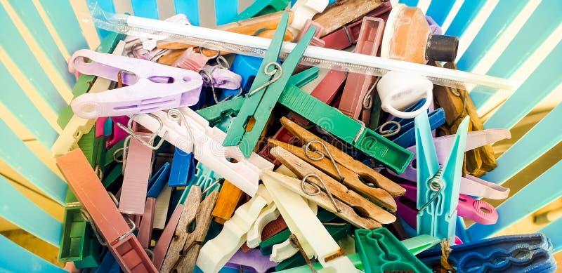 Einige Wäscheklammern in einer blauen Schüssel mit Sonnenstrahlen dazu stockfotografie