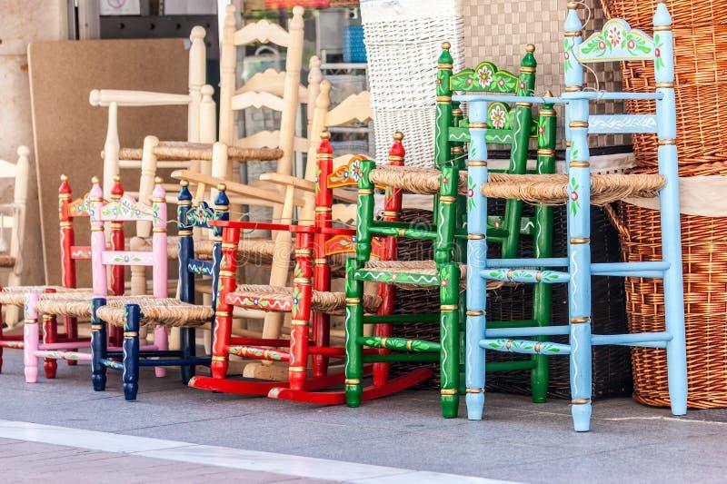 Einiges Holz und geflochtene Stühle in den verschiedenen Farben stockfoto