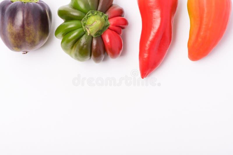 Einiges reifer Bonbon und Peperoni von Rotem und von Orange auf einem wei?en Hintergrund lizenzfreies stockfoto