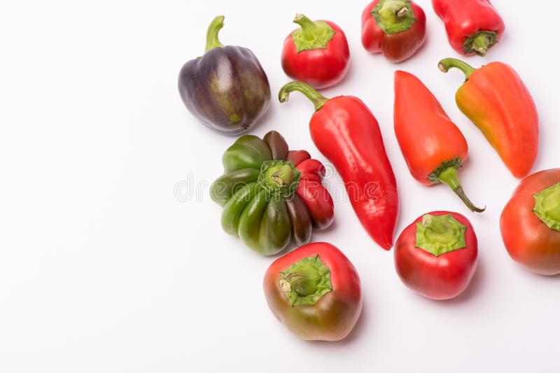 Einiges reifer Bonbon und Peperoni von Rotem und von Orange auf einem wei?en Hintergrund stockbild