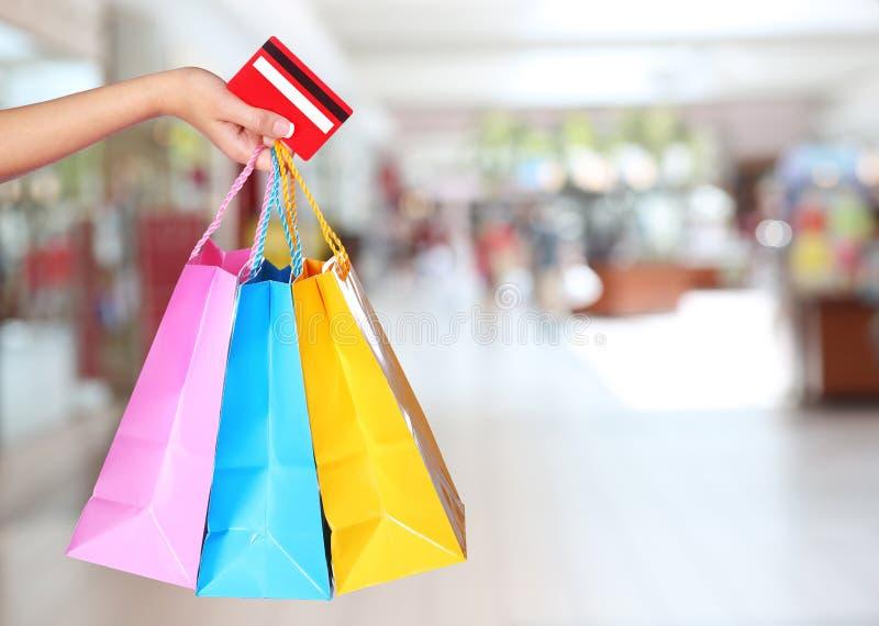 Einkauf! Weibliche Hand, die bunte Einkaufstaschen hält stockbild