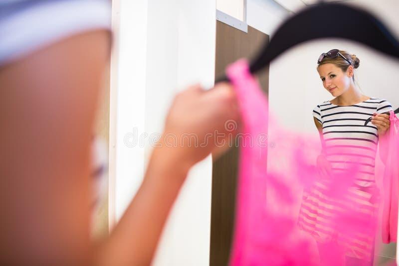 Einkaufen der jungen Frau in einem Modespeicher, versuchend auf etwas Kleidung stockbild