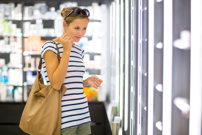 Einkaufen der jungen Frau für den rechten Duft stockfotos
