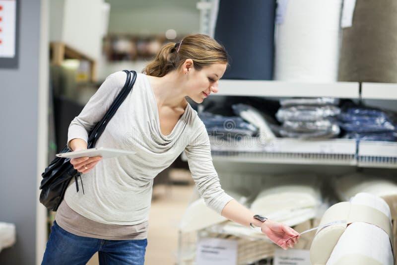 Einkaufen der jungen Frau für Möbel in einem Möbelgeschäft lizenzfreies stockbild