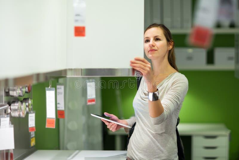 Einkaufen der jungen Frau für Möbel in einem Möbelgeschäft stockfotografie