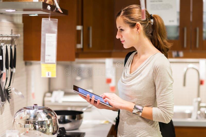 Einkaufen der jungen Frau für Möbel in einem Möbelgeschäft lizenzfreie stockfotos