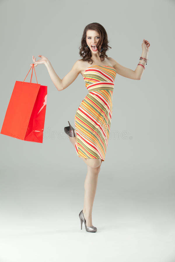 Einkaufen der jungen Frau, schauend sehr glücklich stockfotografie