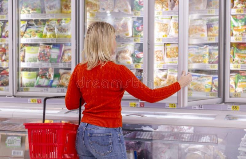 Einkaufen der jungen Frau am Supermarkt lizenzfreies stockfoto