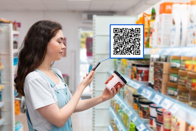 Einkaufen Eine hübsche junge Frau scannt die Zusammensetzung der Creme für den Körper Moderne Technologie im Alltagsleben stockbild