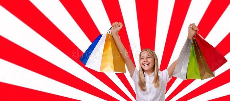 Einkaufen, Feiertag und Tourismuskonzept - junges Mädchen mit Einkaufstaschen über geometrischem Hintergrund stockfotografie