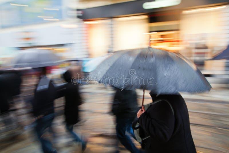 Einkaufenleute, die in die regnerische Stadt gehen lizenzfreie stockfotografie