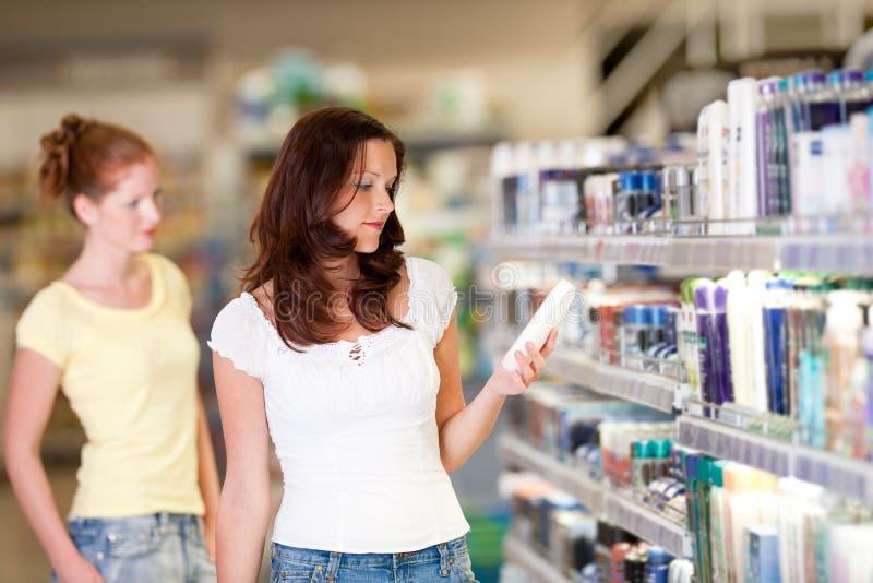 Einkaufenserie - Frauenholdingflasche des Shampoos stockbilder