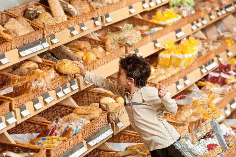 Einkaufenserie - kaufendes Brot des kleinen Jungen stockbilder