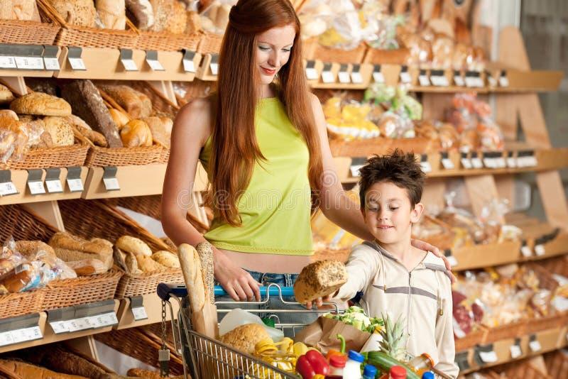 Einkaufenserie - rote Haarfrau mit kleinem Jungen lizenzfreies stockfoto