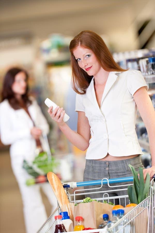 Einkaufenserie - rotes Haarfrauen-Holdingshampoo lizenzfreie stockbilder