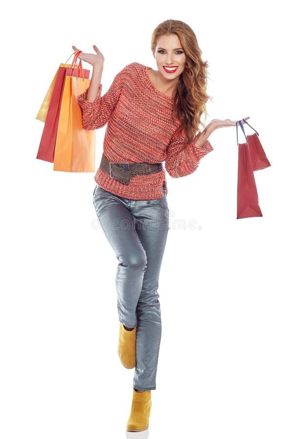 Einkaufsfrau, welche die Taschen, lokalisiert auf Weiß hält lizenzfreie stockfotografie