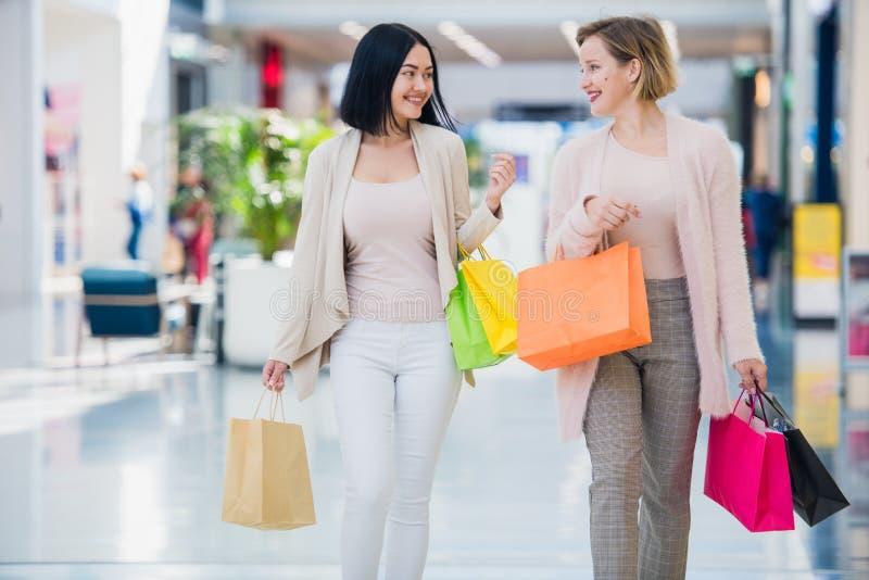 Einkaufsfrauen, welche die glücklichen haltenen Einkaufstaschen haben das Spaßlachen sprechen Zwei schöne Freundinnen der jungen  lizenzfreie stockfotos