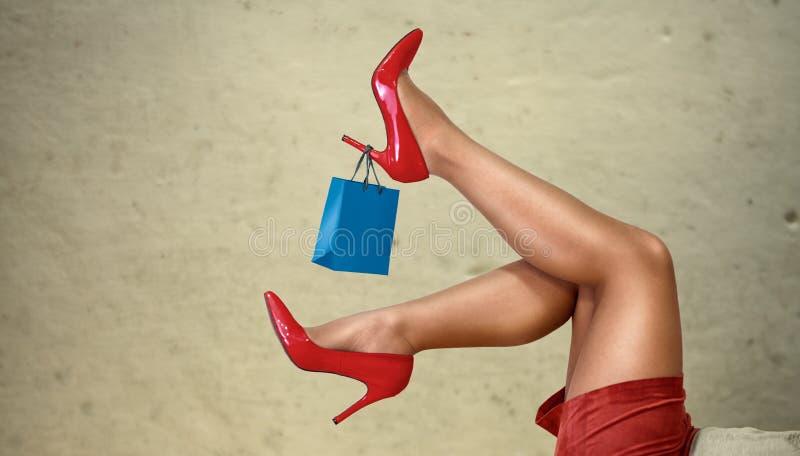 Einkaufsfrauenbeine und kleine Einkaufstasche auf Ferse stockfotos