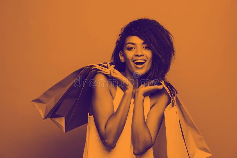 Einkaufskonzept - Headshot der Porträt-jungen schönen attraktiven Afrikanerin lächelnd und froh mit buntem lizenzfreies stockfoto
