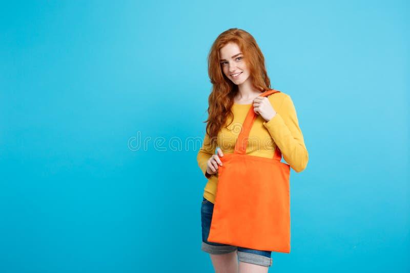 Einkaufskonzept - nahes hohes Porträt junges schönes attraktives redhair Mädchen, das mit orange Einkaufstasche lächelt blau stockfotografie