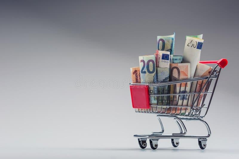 Einkaufslaufkatze voll von geld- Eurobanknoten - Währung Symbolisches Beispiel des Ausgebens des Geldes in den Shops oder günstig lizenzfreies stockbild