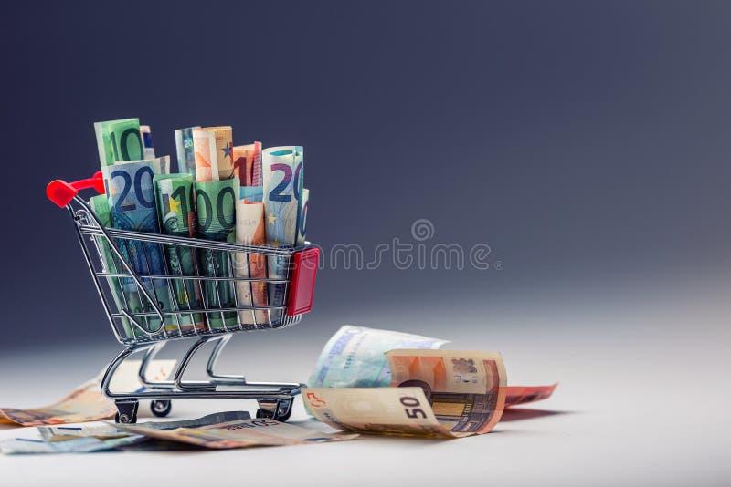 Einkaufslaufkatze voll von geld- Eurobanknoten - Währung Symbolisches Beispiel des Ausgebens des Geldes in den Shops oder günstig lizenzfreies stockfoto