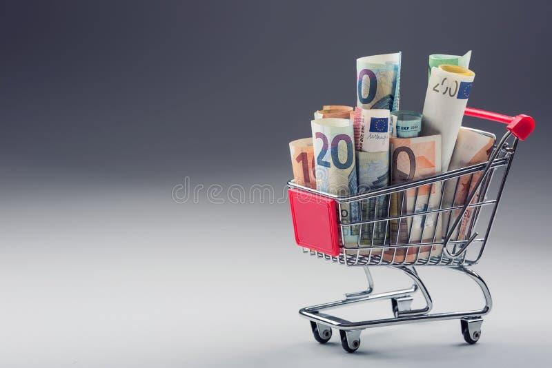 Einkaufslaufkatze voll von geld- Eurobanknoten - Währung Symbolisches Beispiel des Ausgebens des Geldes in den Shops oder günstig stockbild