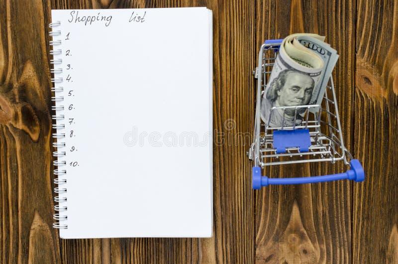 Einkaufsliste mit leerem Warenkorb auf hölzernem Hintergrund stockbild
