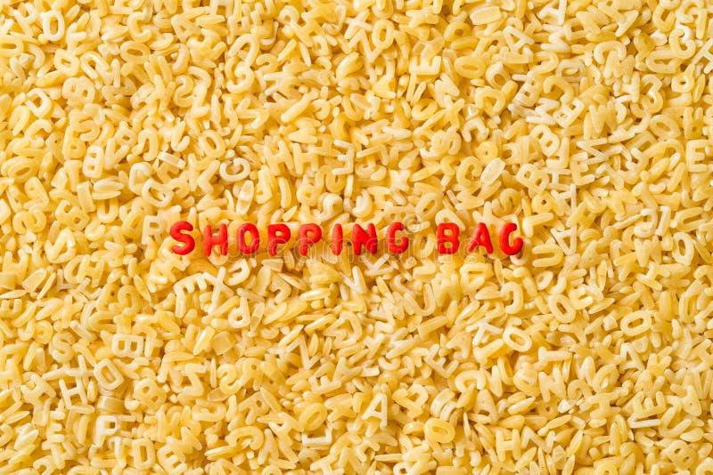 Einkaufstasche buchstabiert mit Alphabetteigwaren stockfotos