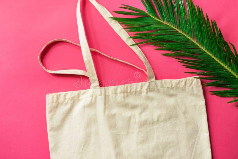 Einkaufstasche-Gr?npalmblatt des leeren wei?en Modells Leinenbaumwollauf pinkfarbenem rosa Hintergrund Freundliche Materialien de stockfoto