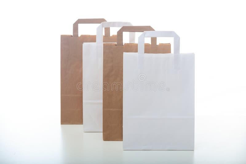 Einkaufstaschen Browns und des Weißbuches auf weißem Hintergrund lizenzfreie stockfotografie