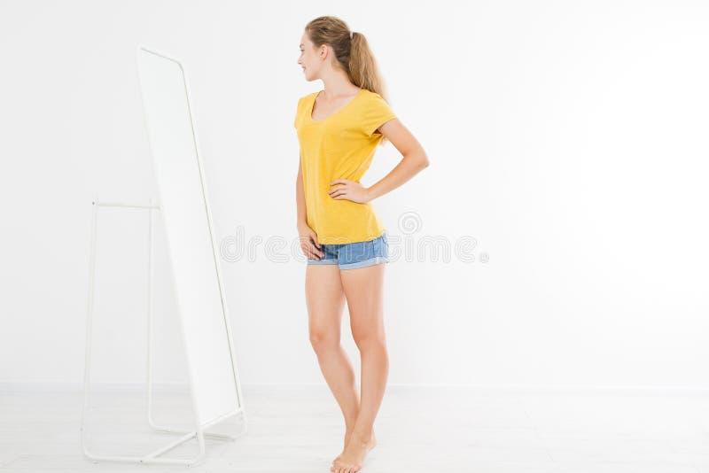 Einkaufsverkaufskonzept Blondes Mädchen in den Jeans und im T-Shirt Junge Frau in der guten Körperform, die Spiegel betrachtet un stockbild