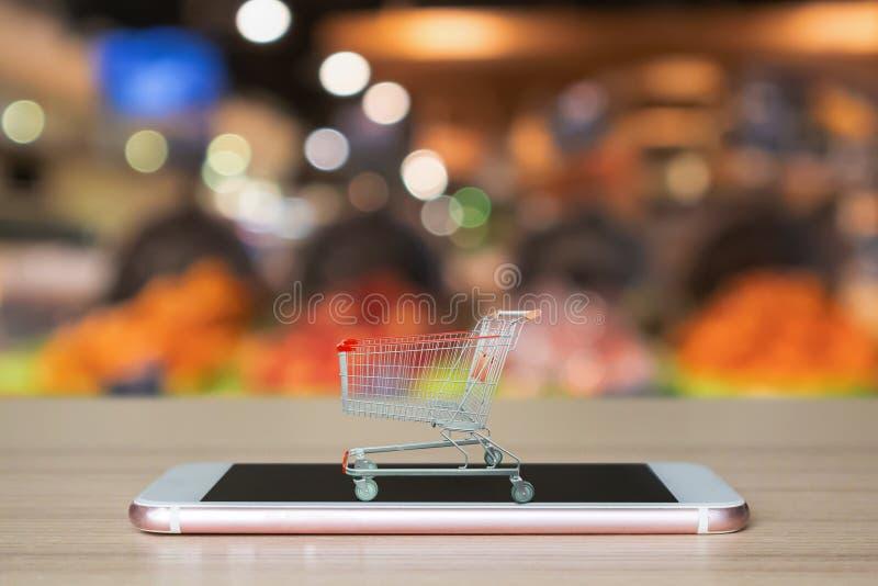 Einkaufswagen auf mobilem Smartphone auf hölzerner Tabelle mit Supermarktgang stockfotos