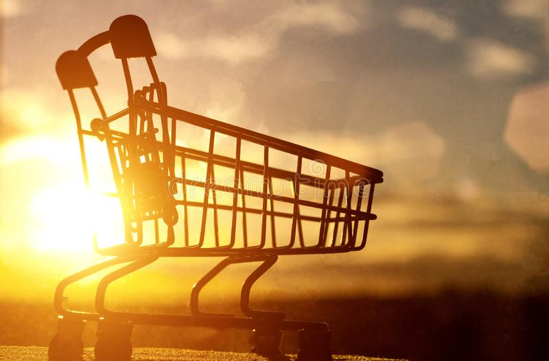 Einkaufswagen gegen das Sonnenuntergang- und Himmelkonzept des Importes und des Exports der natürlicher Ressourcen des Landes, Ko stockfotos