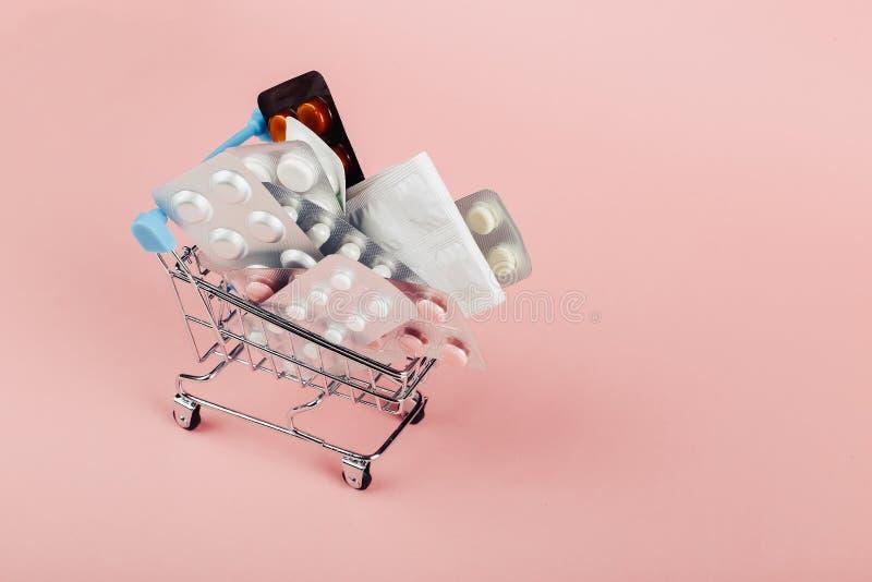Einkaufswagen geladen mit Pillen auf einem rosa Hintergrund Das Konzept von Medizin und der Verkauf von Drogen Kopieren Sie Platz lizenzfreie stockbilder
