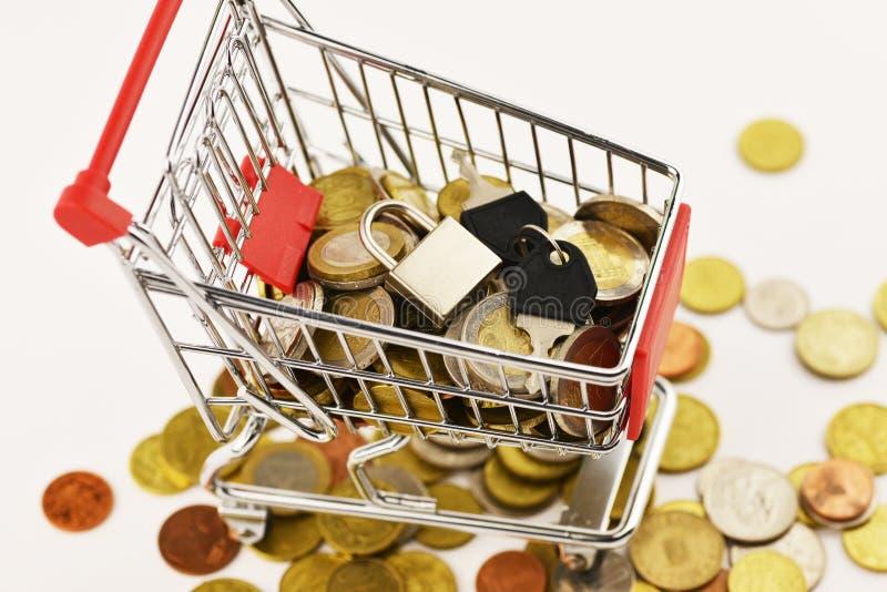 Einkaufswagen mit Euro und Dollar Münzen, die auf weißem Hintergrund, Absatzsoll lokalisiert wurden, erreichte Konzept lizenzfreie stockfotografie
