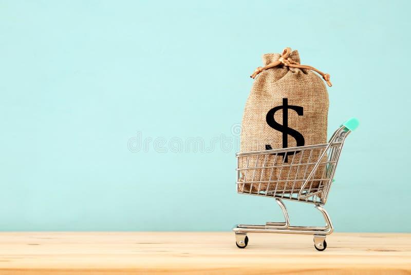 Einkaufswagen mit Tasche voll des Geldes mit Dollar unterzeichnen über blauem hölzernem Hintergrund stockfotos