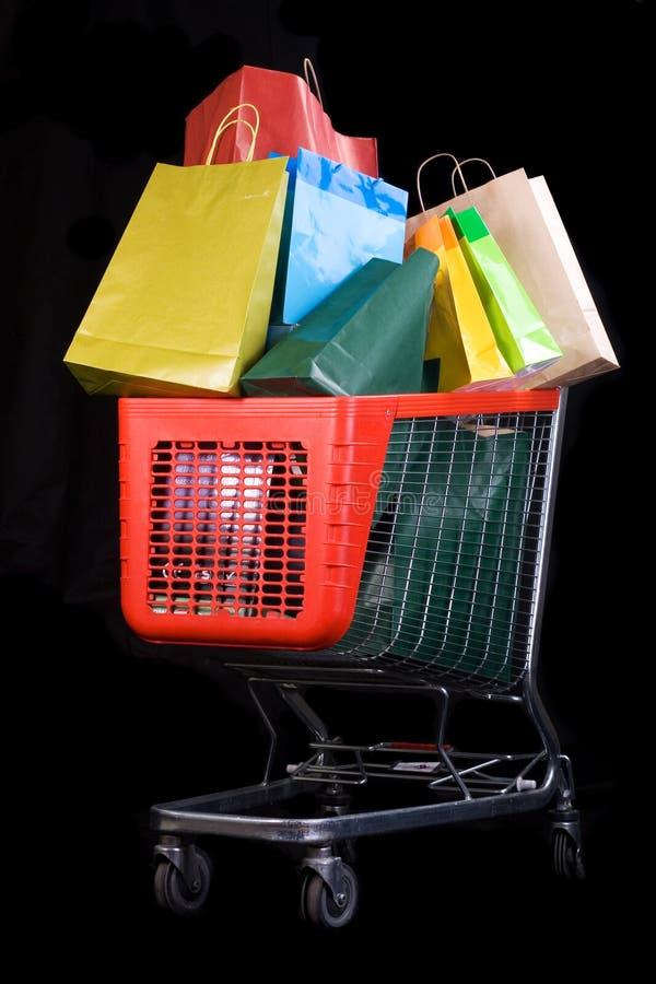 Einkaufswagen voll der Geschenke auf schwarzem Hintergrund lizenzfreies stockfoto