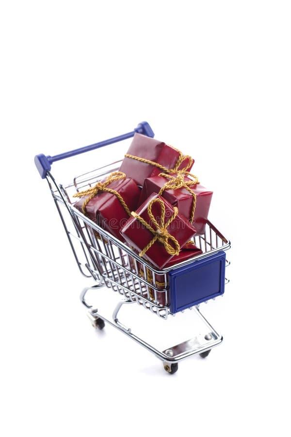 Einkaufswagen voll mit rotem Weihnachtsgeschenkkasten stockbilder