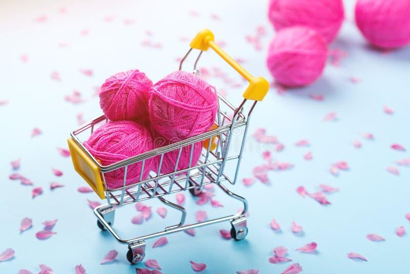 Einkaufswagen voll von Wollstrickenden Bällen Strickender Hintergrund Rosa Wollgarne Bunte rosa Faden auf blauem Papierhintergrun stockbild