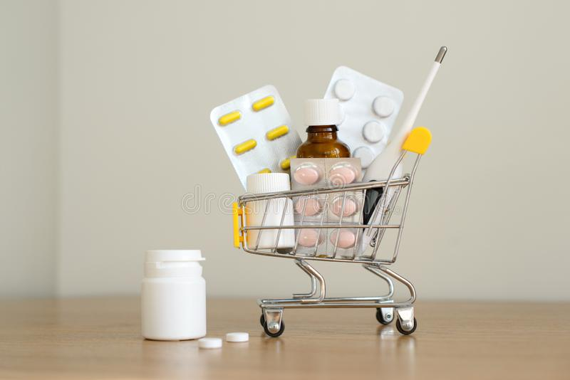 Einkaufswagenspielzeug mit Medikamenten: Pillen, Blisterpackungen, medizinische Flaschen, Thermometersatz Gesundheitswesen- und M lizenzfreie stockbilder